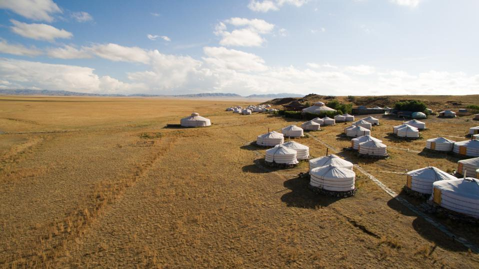 White round tent-like structures dot the right hand side of the photo. The left is empty land below a blue sky with a few clouds.