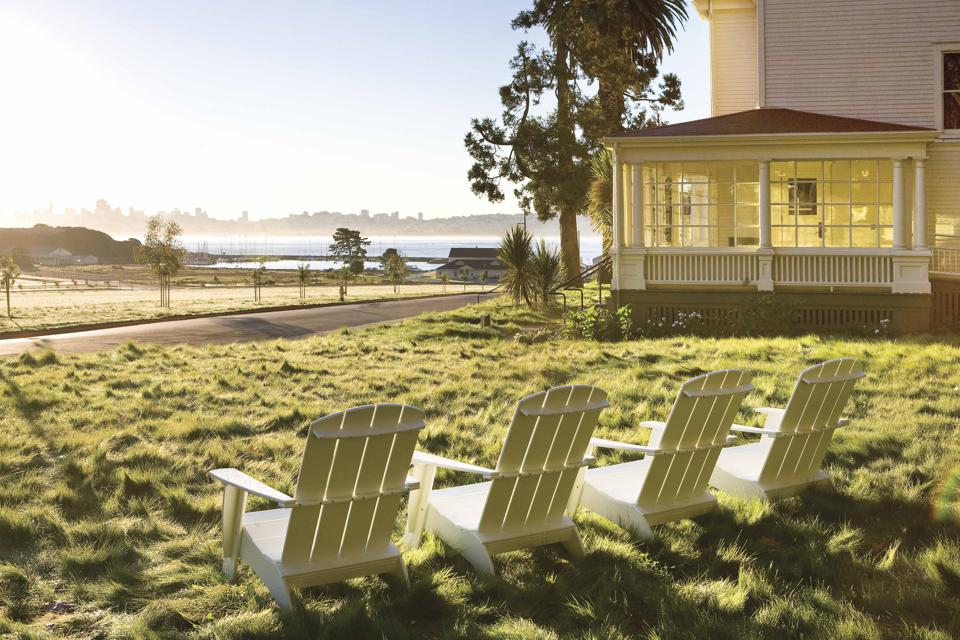 Four white wooden chairs look out onto green grass, a small white building with a porch, and the bay with the San Francisco skyline in the background