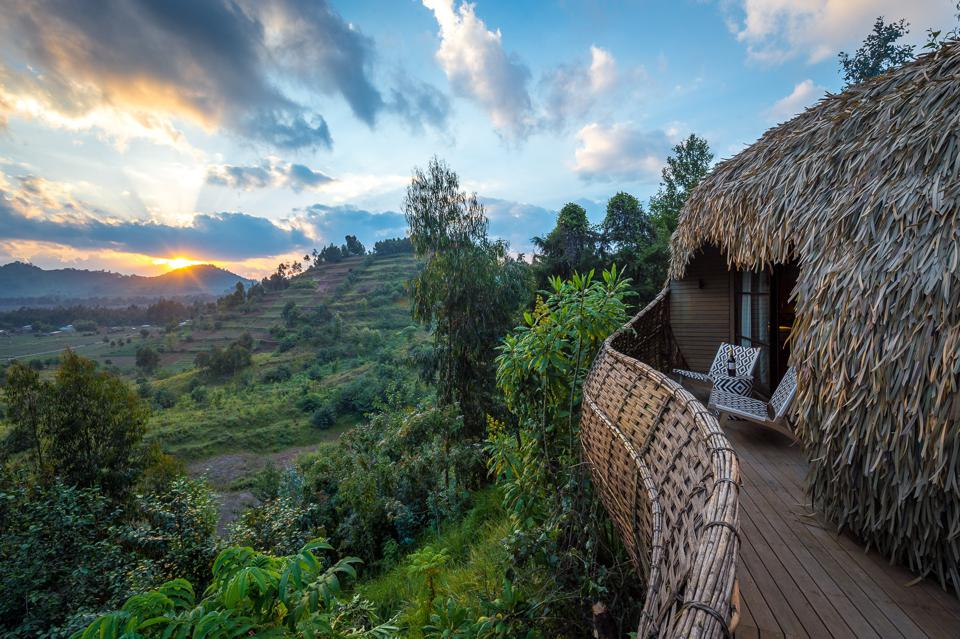 Two chairs on a balcony of a thatched cottage look out over lush green plants, a terraced hill, and the sun setting behind a mountain