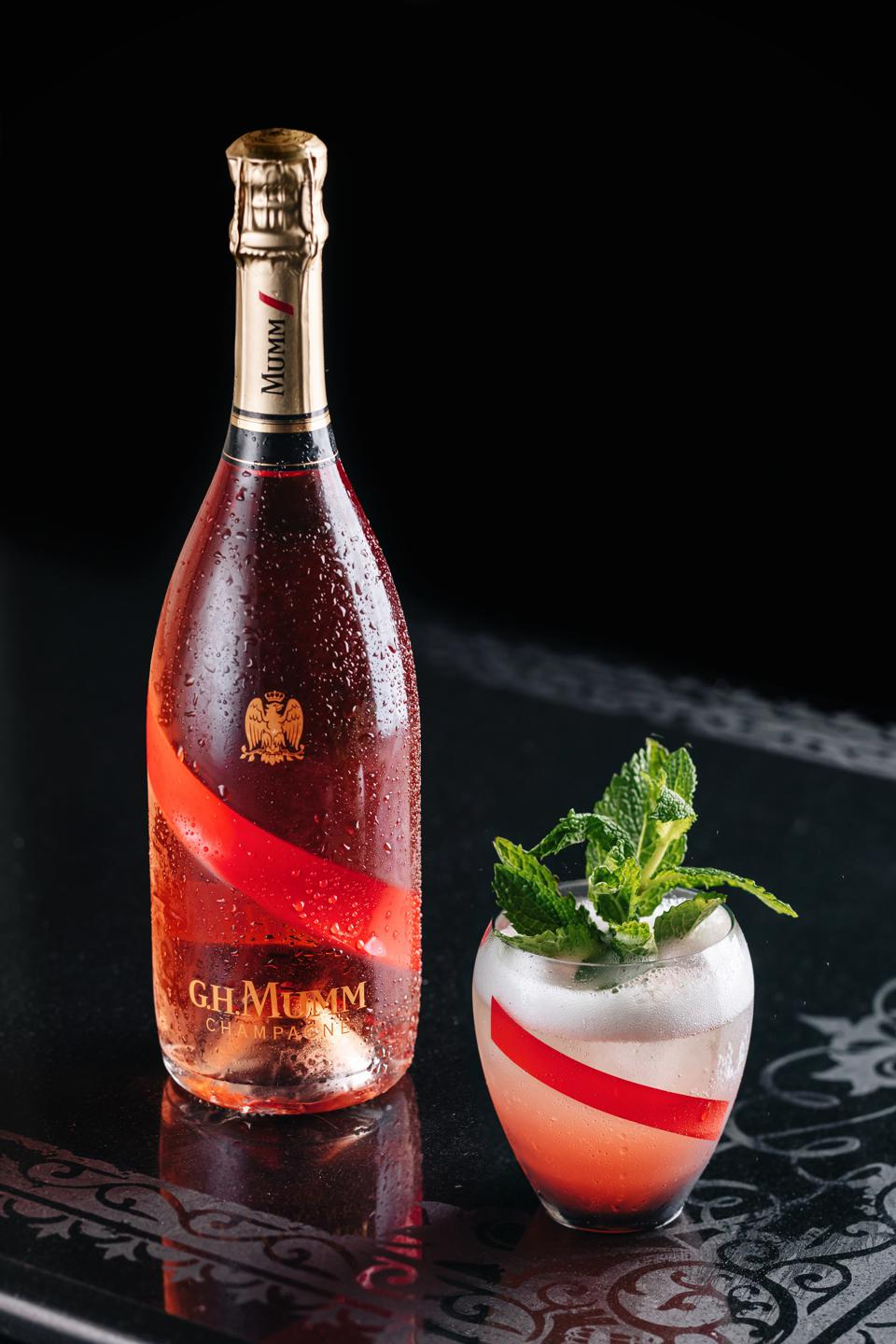 Bottle of G.H. Mumm Grand Cordon Rouge Champagne with sparkling rosé cocktail
