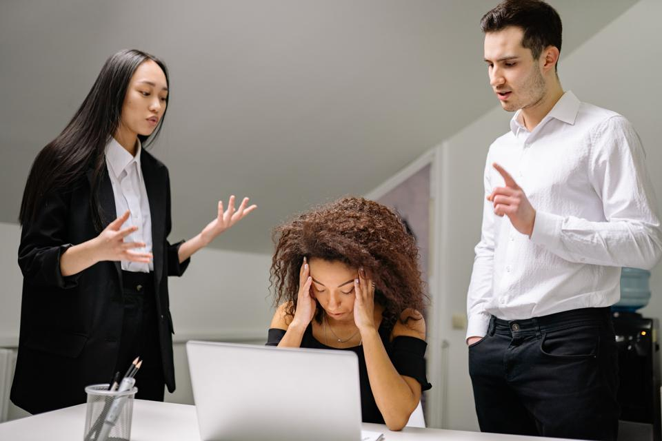Stressed woman at a computer with two people standing over talking at her
