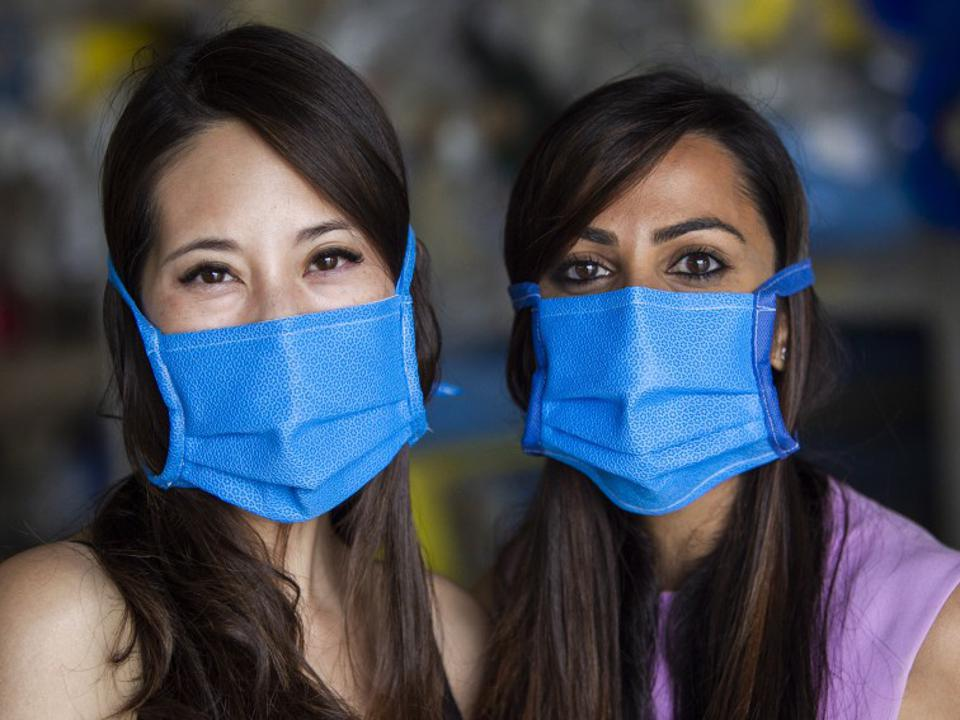 Two young women wearing blue face masks.