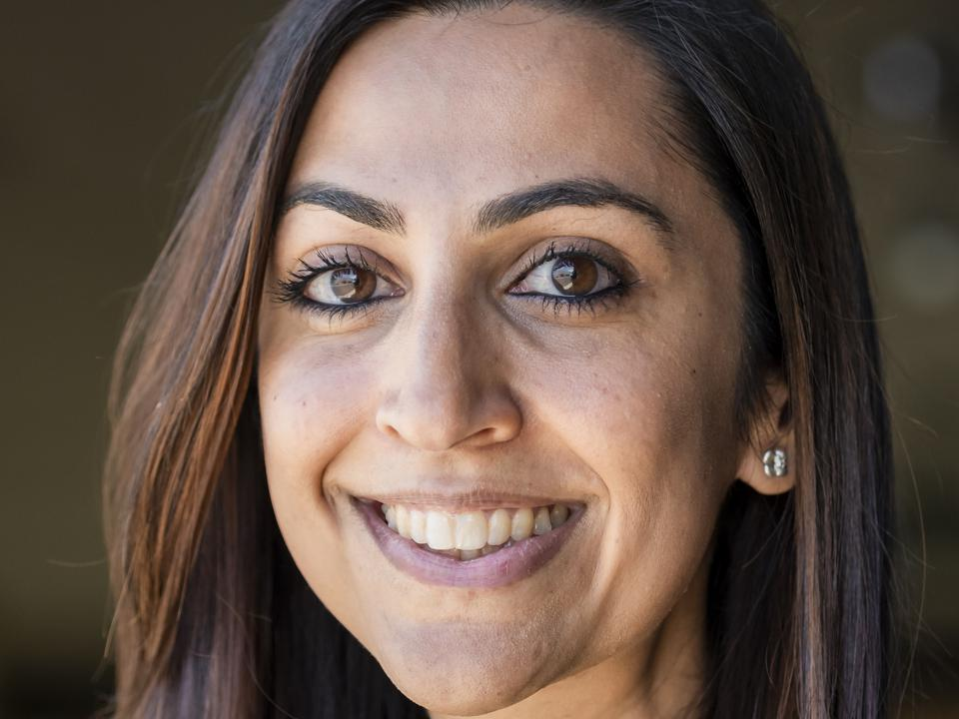 Headshot of Sharma with long brown hair.