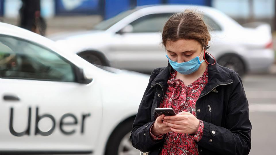 A woman wearing a face mask uses her mobile phone as an Uber...