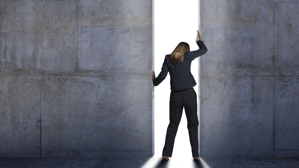 Businesswoman Pushing Open Concrete Walls