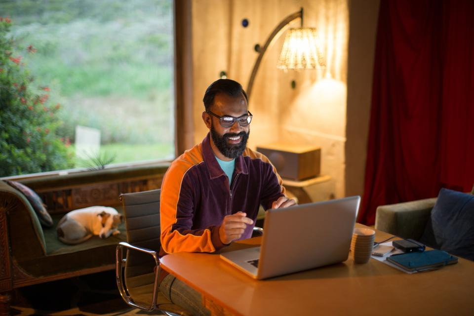 Mixed race man working from home on his computer during lockdown