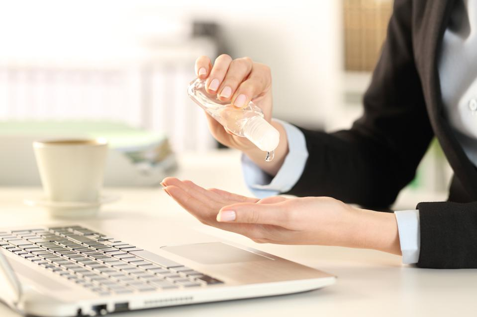 Business woman cleaning hands with sanitizer in the office