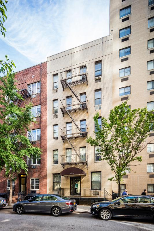 Five-story walkup multifamily building with fire escapes.