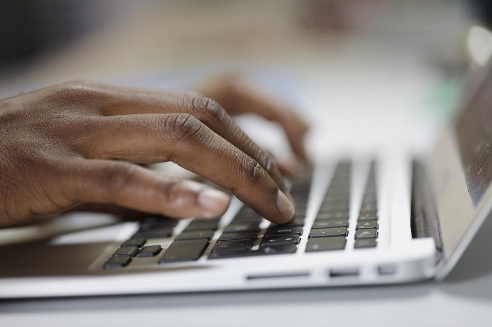 Closeup of Black woman typing on Laptop