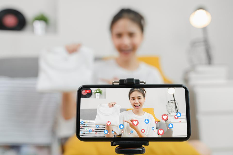 Young Asian women showing clothes and sale online on social with smartphone to customers from home. Network technology concept.