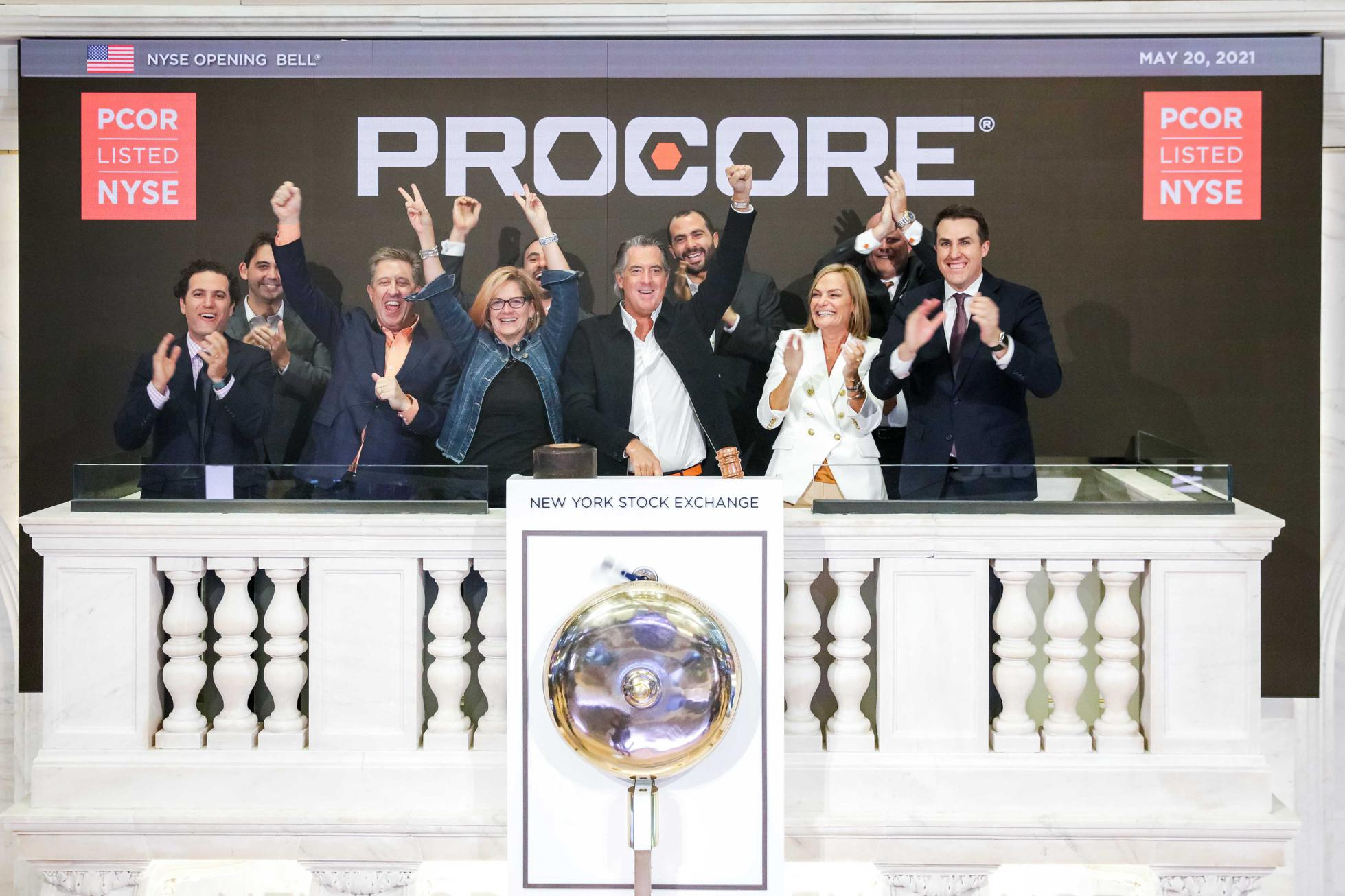 Procore CEO Tooey Courtemanche (center) rings the bell of the New York Stock Exchange.