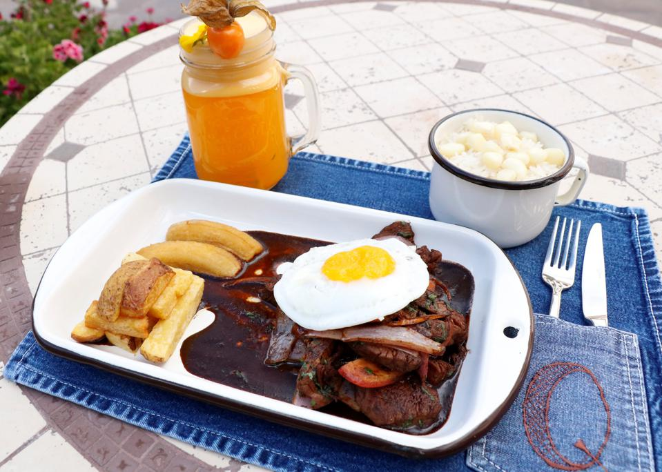 On a patio table is a denim place mat with an orange drink, a cup of what looks to be white rice and cubes of potato, and a plate with fried potato, plantain, brown meat with vegetables with a brown sauce and topped with a fried egg.