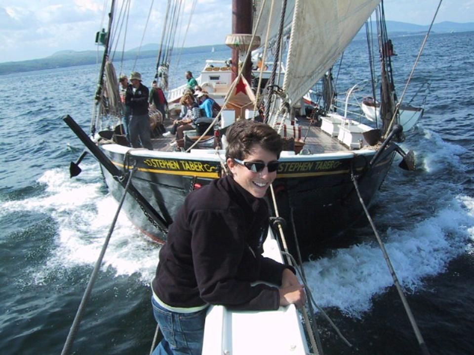 A smiling passenger on the Stephen Taber's bowsprit
