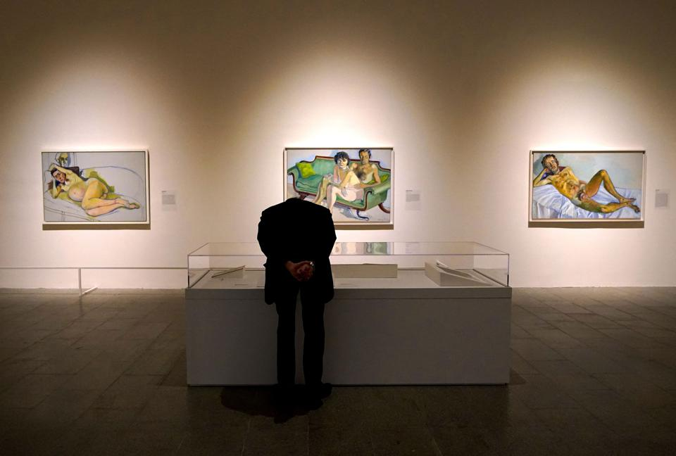 A person looks at paintings during a press preview for ″Alice Neel: People Come First″ at  Metropolitan Museum of Art in New York on March 15, 2021. - The exhibition marks the first museum retrospective in New York of American artist Alice Neel (1900Ð1984) in 20 years. (Photo by TIMOTHY A. CLARY/AFP via Getty Images)