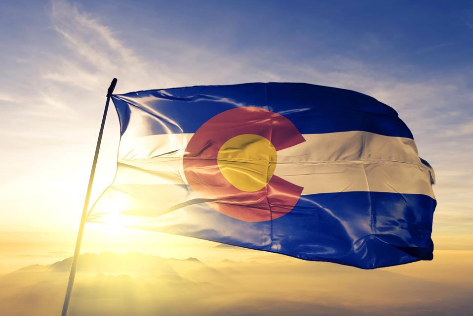 Colorado state of United States flag textile cloth fabric waving on the top sunrise mist fog