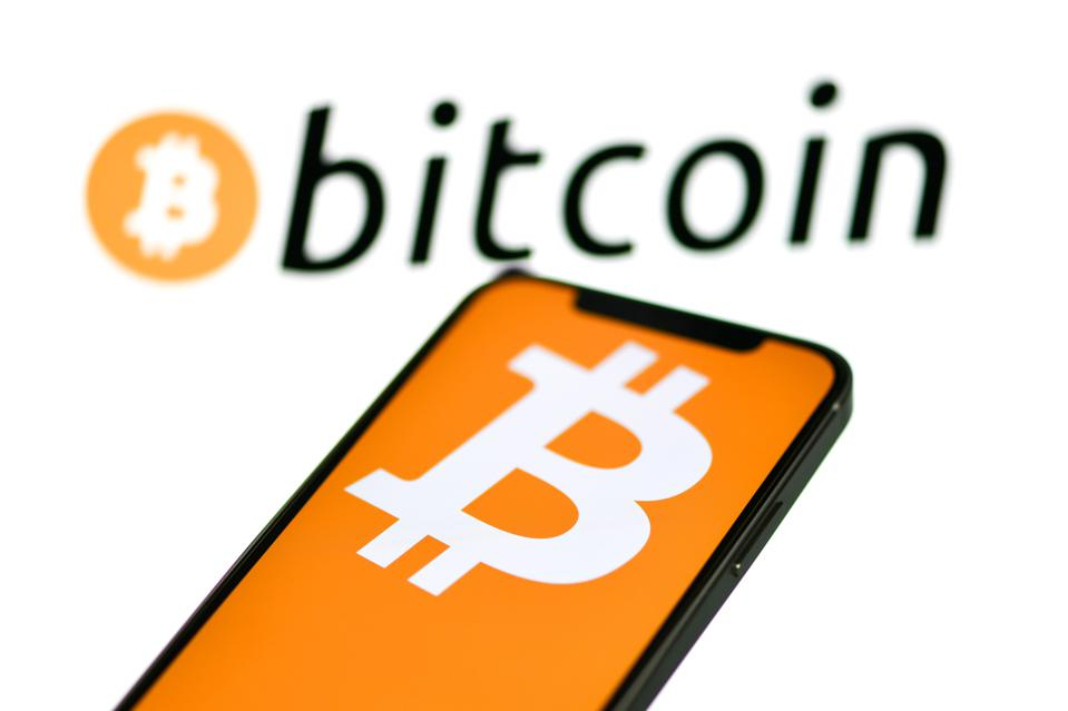 In the photo illustration a bitcoin logo is seen displayed...