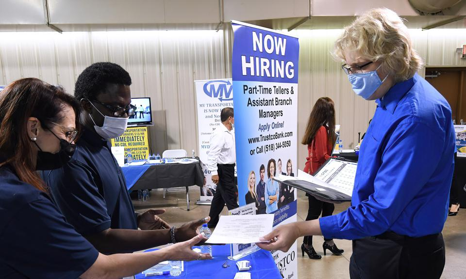 A man hands his resume to an employer at the 25th annual...