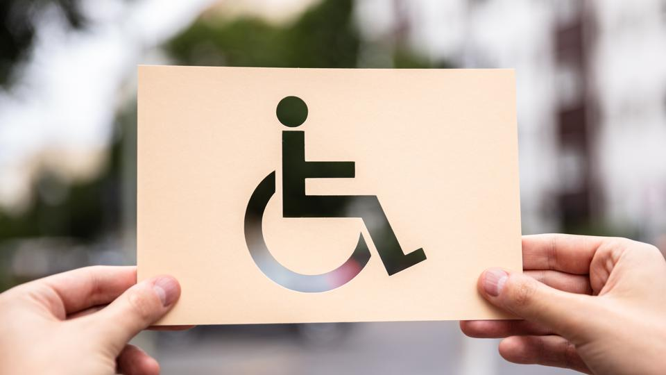 Hands Holding Paper With Cutout Disabled Sign