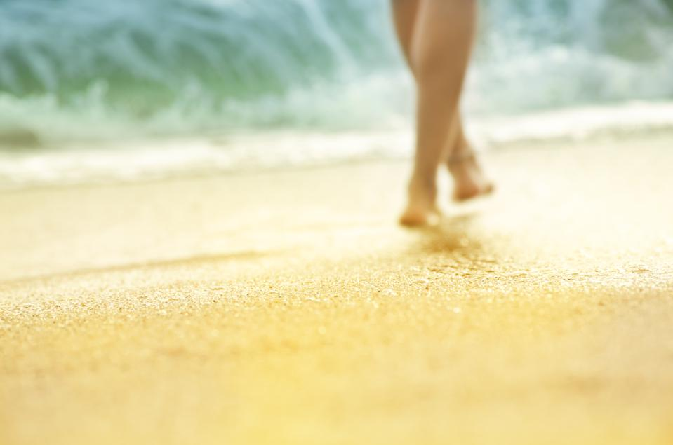 Blurred photo with shallow depth of field. Vacation holidays background wallpaper - silhouette of sunburnt legs of woman walking along sea beach lit by sun.
