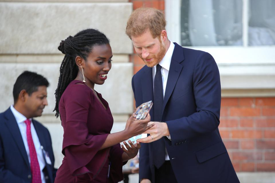 Rosette Muhoza receives an award from Prince Harry at a garden party in England.