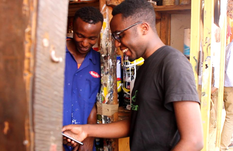 Two Kigali residents smile as one uses an app to confirm delivery of scrap metal.