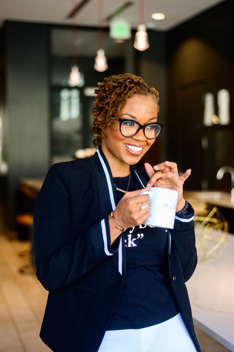 A Black woman with glasses holding a coffee cup, smiling