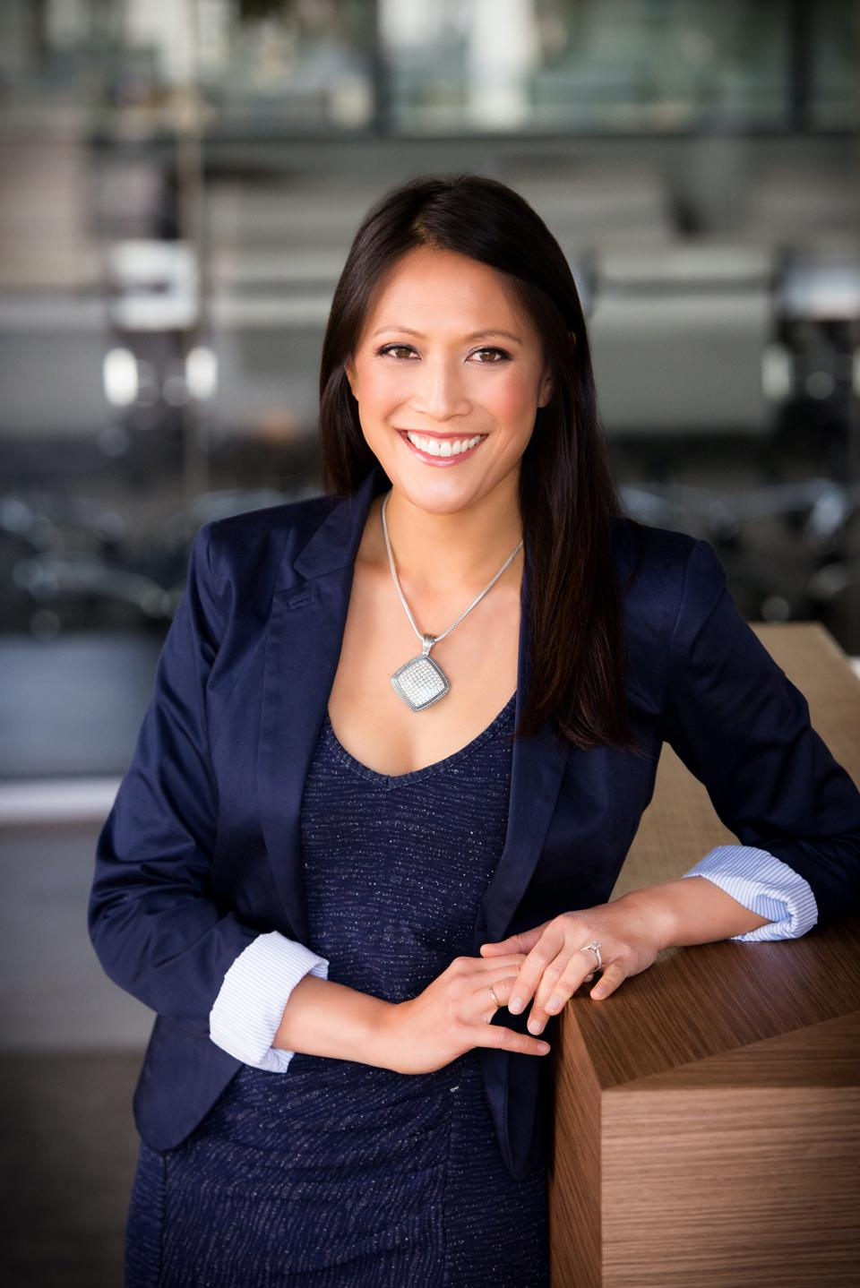 Asian American woman in a navy suit, smiling
