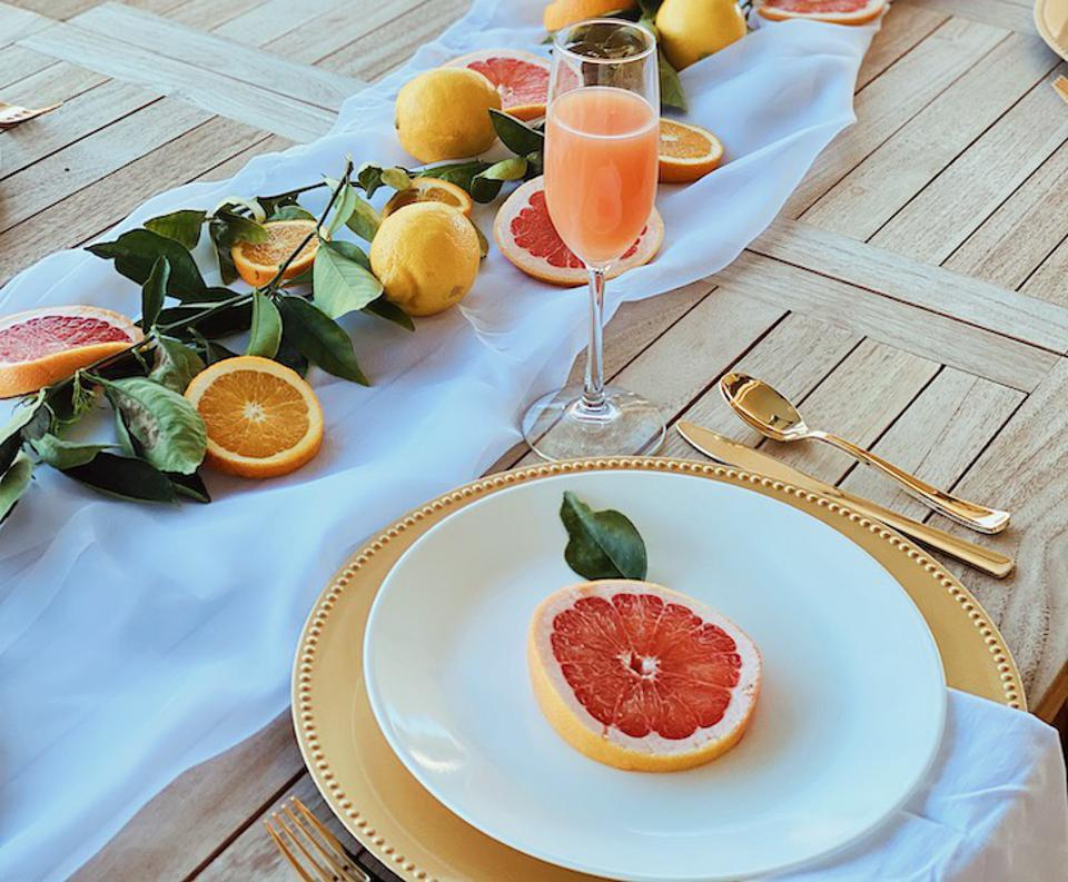 A wood table set with white plates, a gold charger, gold flatware and a white runner with cup citrus fruits and leaves.