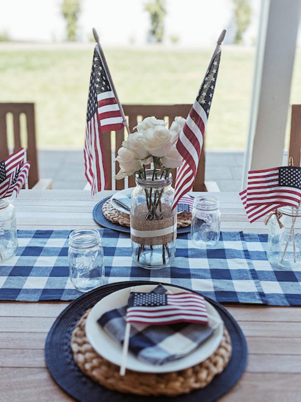 Table with a gingham runner, napkins, decorative American flags and white plates on blue and rattan chargers.