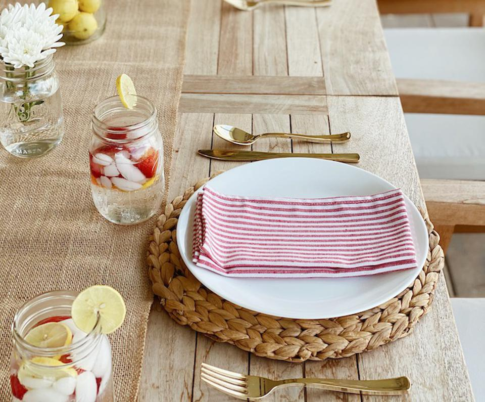 A wood table with red striped napkins, gold flatware, a rattan runner, and mason jars.
