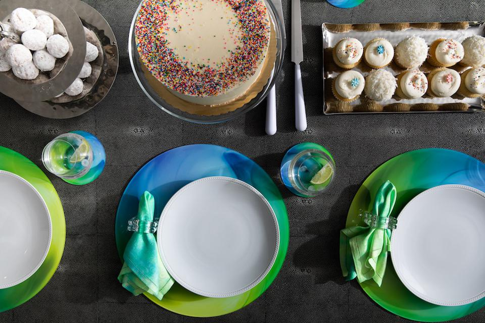 A table with candy swirl placemats, coasters, cakes and cupcakes with a grey placemat.