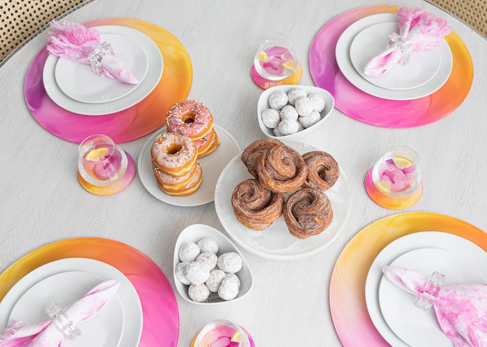A tablscape with pink candy swirl placemats and coasters with doughnuts against a white tablecloth and tie dye napkins