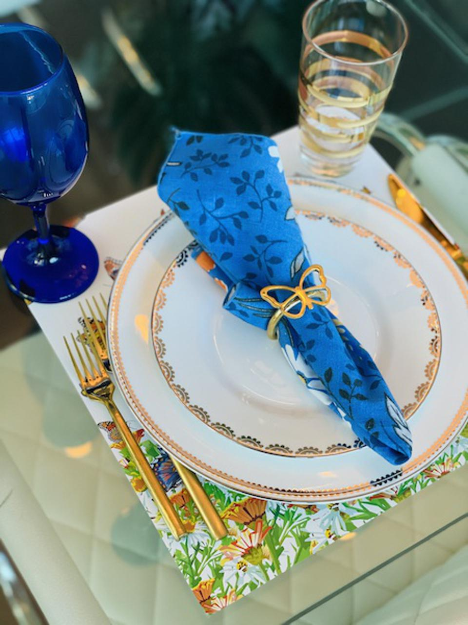 A placesetting with gold utensils and a butterfly napkin ring