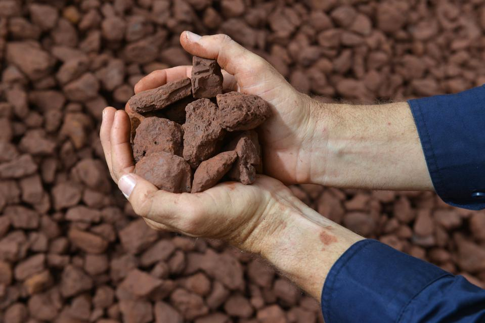 Two hands holding an iron ore sample.
