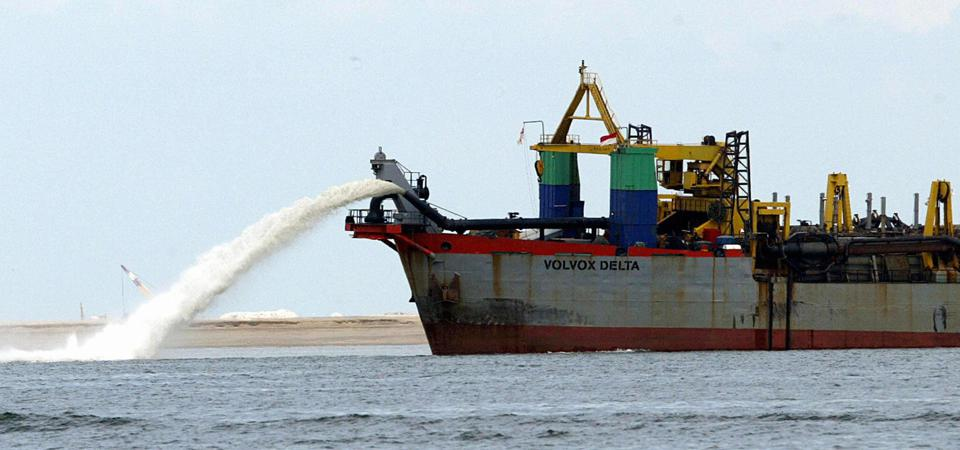 A ship spewing sand fills the seabed for land reclamation off of western Singapore.