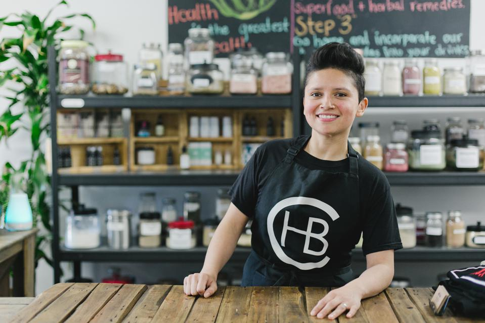 A woman posing in her wellness business with herbs behind her.