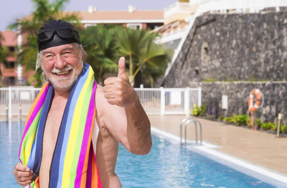 Smiling senior man with white hair comes out of the pool wearing swimming cap and goggles gesturing ok with hand - with a colorful towel on his shoulders - active seniors in retirement