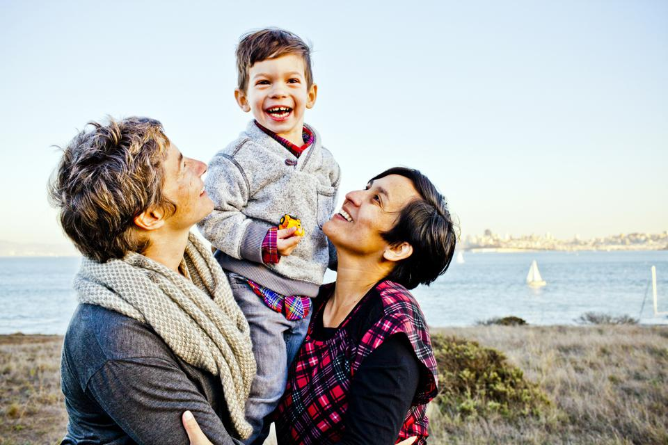 Portrait of lesbian family with toddler son (2-3) smiling outdoors, San Francisco, California, USA