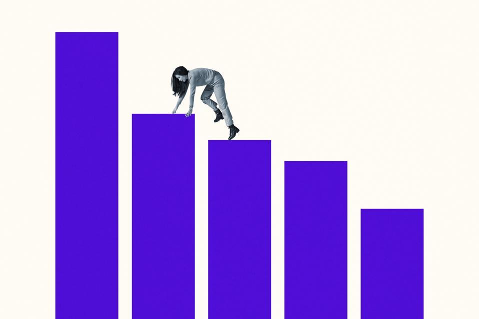 Young woman climbing on blue bar graphs