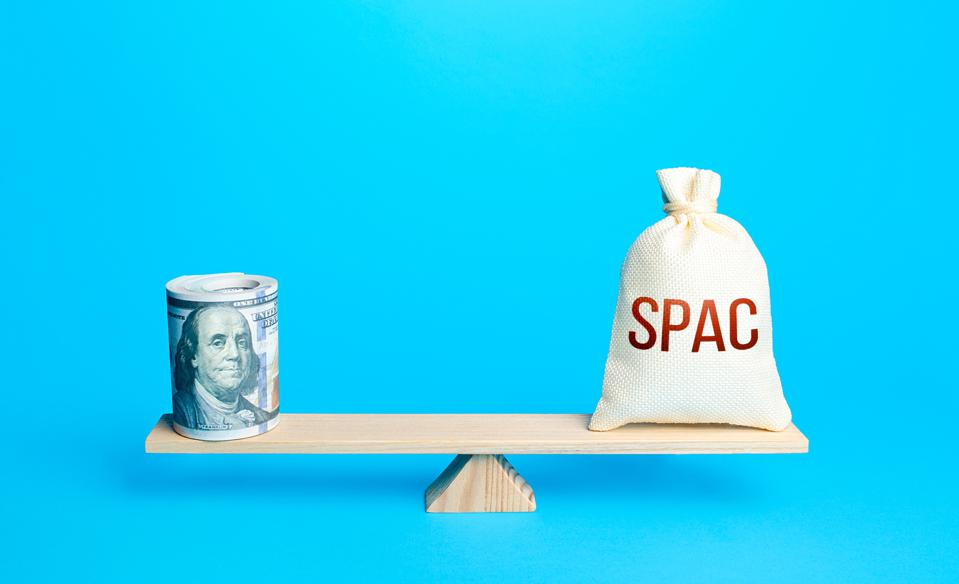 Bundle of dollars and a bag of SPAC on scales. The concept of attracting investors' money to fund the merger of companies into a new one. Assessing the value of the new company and profitability.