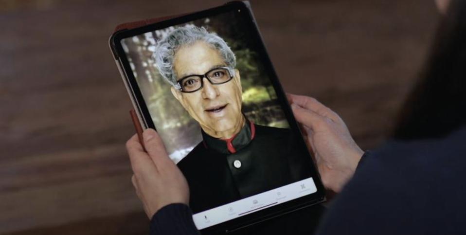Person holding an iPad interacting with Deepak Chopra's AI