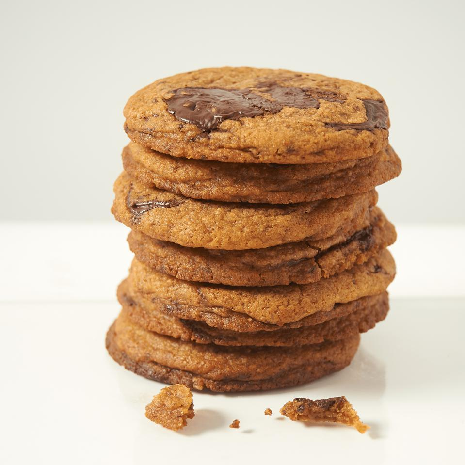 A stack of classic chocolate chip cookies, with some crumbs