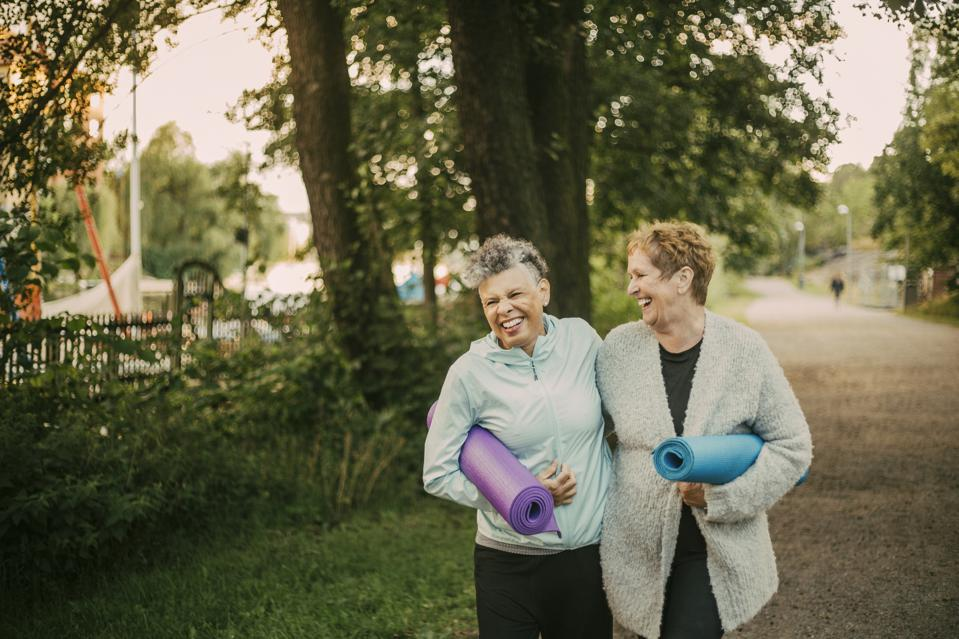 Smiling female friends holding exercise mat while walking on footpath