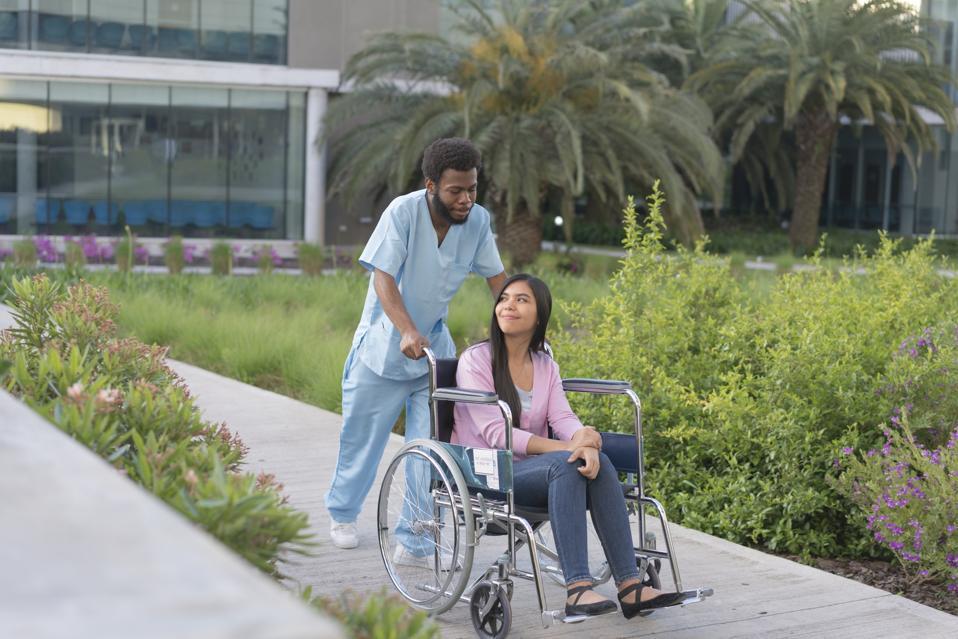 Black male nurse assists a young woman patient through a hospital garden.