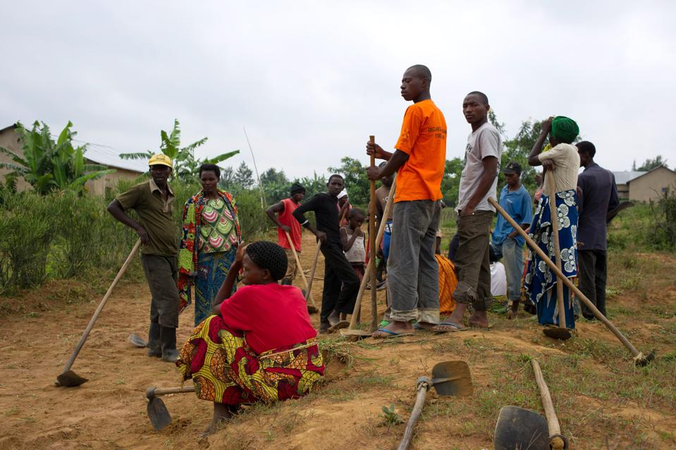 Rwandan villagers carrying tools get together to participate in Umuganda.