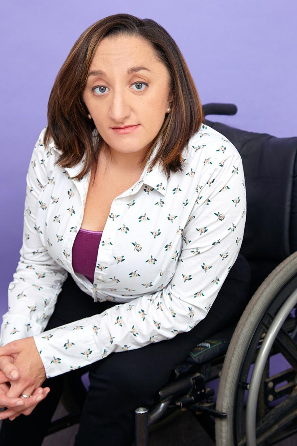 A white woman with brown hair sits in a wheelchair.