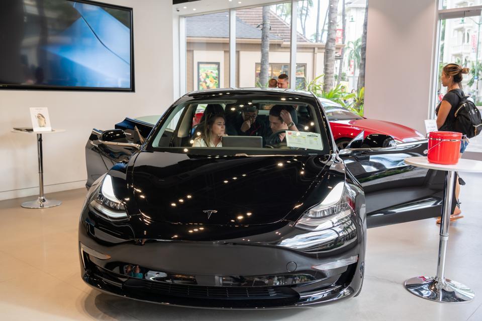 Customers admire a Tesla Model 3 electric vehicle at a Tesla...
