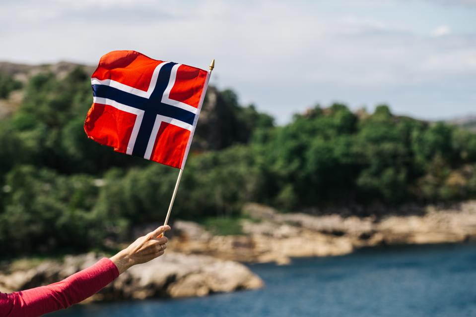 Tourist with Norwegian flag on the sea coast