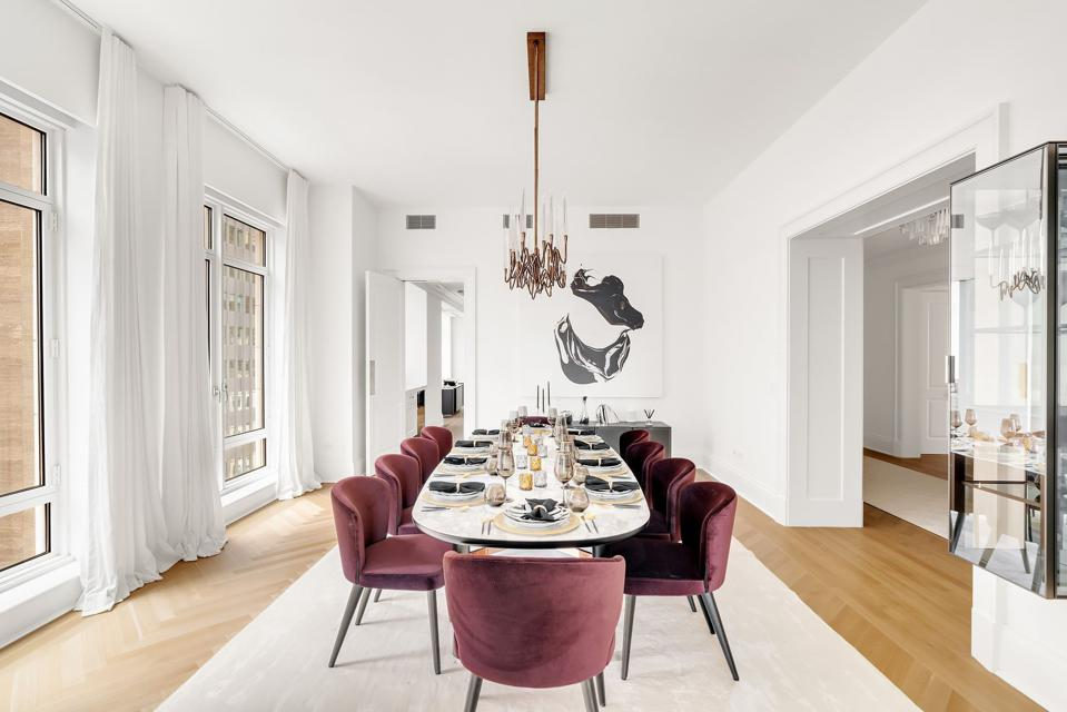 A dining table has red chairs in a white room