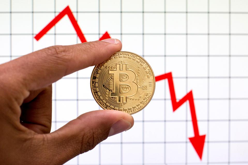In this photo illustration, a Bitcoin is seen with graph in...